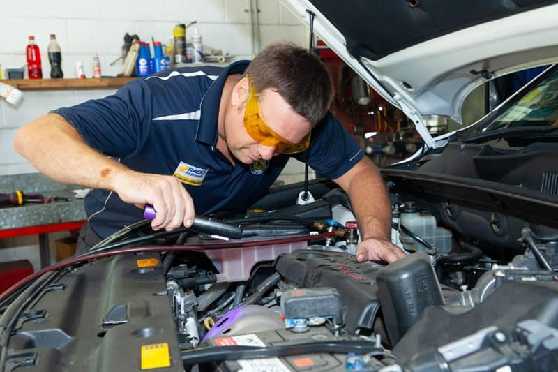 nambour mechanic under car hood holding flashlight doing logbook servicing